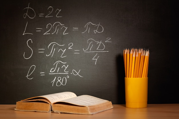 Back to school concept. old schoolbooks and pencils lying on a wooden school desk in front of a black chalkboard with mathematical formulas school.