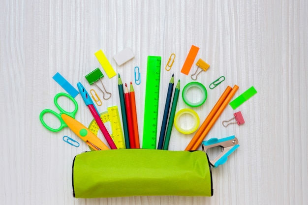 Back to school concept. pencil case with school office supplies on a white wooden background.