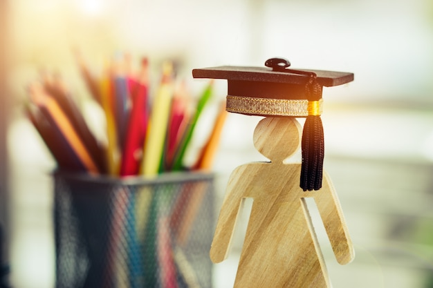 Back to school concept, people sign wood with graduation celebrating cap blur pencil box