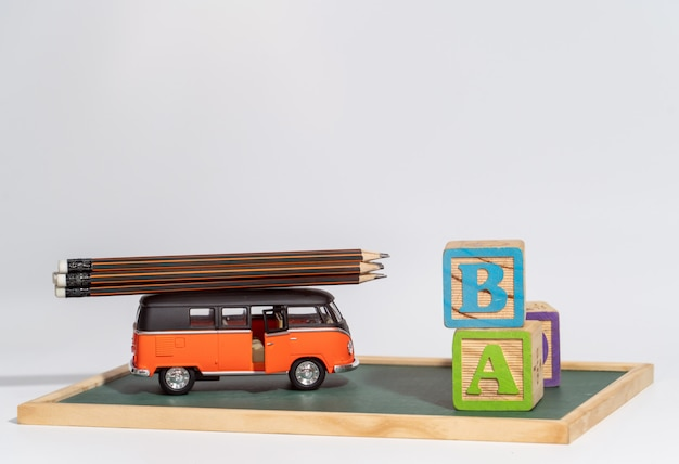 Back to school concept. school bus carry  pencils and letters block on blackboard