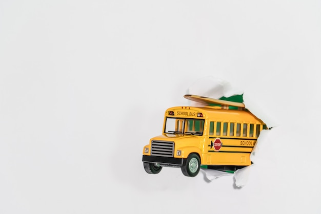 Back to school concept. school bus jumping through white paper