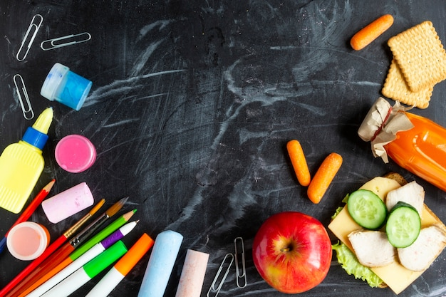 Back to school concept. school lunch, stationery on blackboard