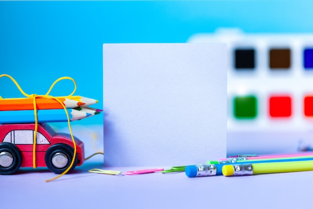 Back to school concept. school and office supplies, colorful pens, pencils, paints on blue