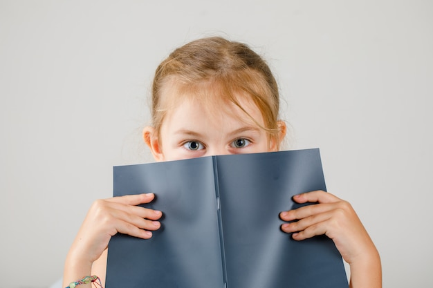 Back to school concept side view. girl hiding her face with copybook.