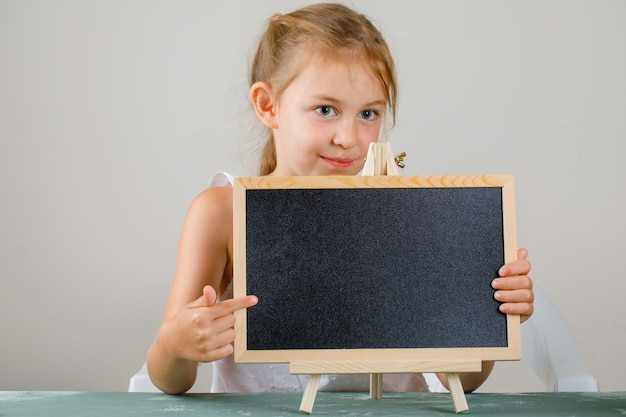 Back to school concept side view. little girl holding and showing blackboard.
