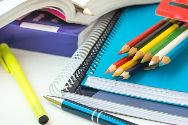 Back to school concept. supplies stack of copybooks multicolored pencils highlighter