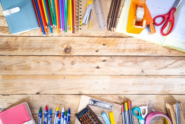 Back to school concept. top view of colored pencil, and supplies  on wooden table