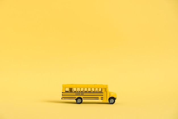 Back to school concept. traditional yellow school bus on yellow background