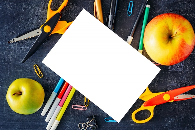 Back to school concept. white blank sheet isolated with two apples and school  supplies on table top view