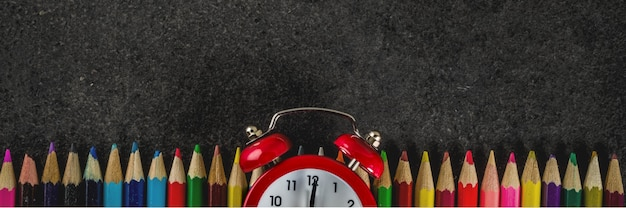 Back to school concept with books alarm clock color pencils c