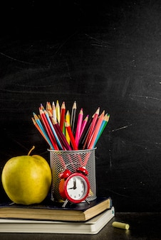 Back to school concept with books alarm clock color pencils chalkboard background