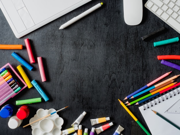 Back to school concept with drawing book, crayons, coloured pencils, poster color, graphic tablet, keyboard, mouse computer and school stationery on black wooden background with copy space
