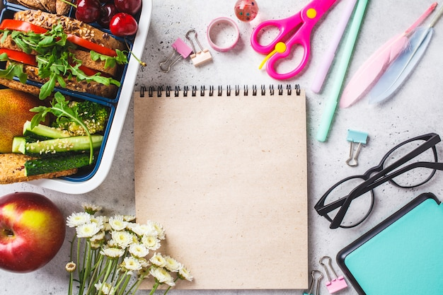 Back to school concept with lunch box with sandwich, fruit, snacks, notebook, pencils and school items