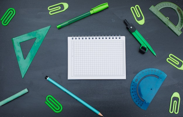 Back to school concept with notebook, pen, pencil, chalk, compass, paper clips, rulers on grey background flat lay.