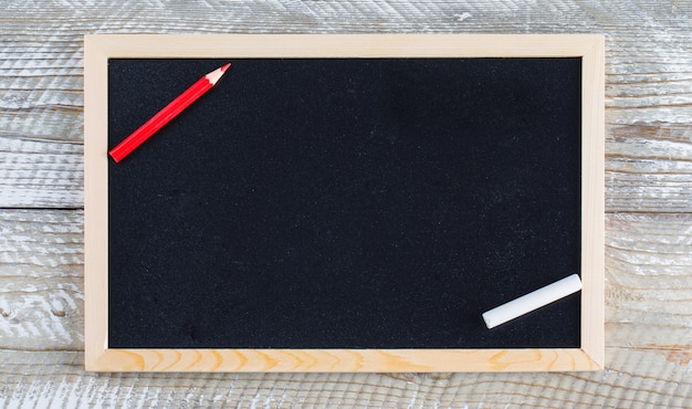 Back to school concept with pencil, chalk on wooden background flat lay.