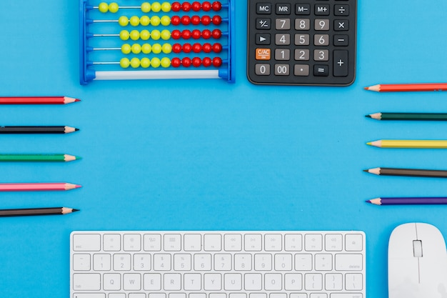 Back to school concept with pencils, keyboard, mouse, calculator, abacus on blue background flat lay.