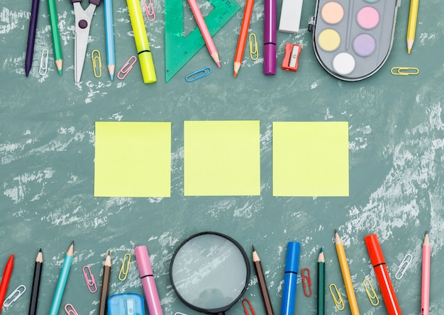 Back to school concept with sticky notes, magnifying glass, school supplies on plaster background flat lay.