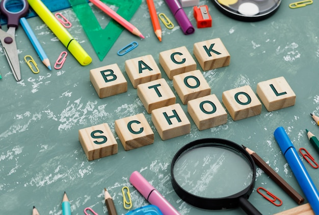 Back to school concept with wooden cubes, magnifying glass, school supplies on plaster background high angle view.