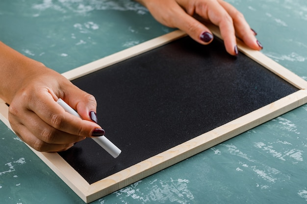 Back to school concept. woman writing on blackboard with chalk.
