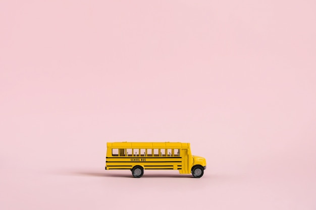 Back to school concept. yellow toy model school bus on pink