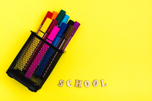 Back to school. container with markers and the word school from wooden letters on a yellow background. top view