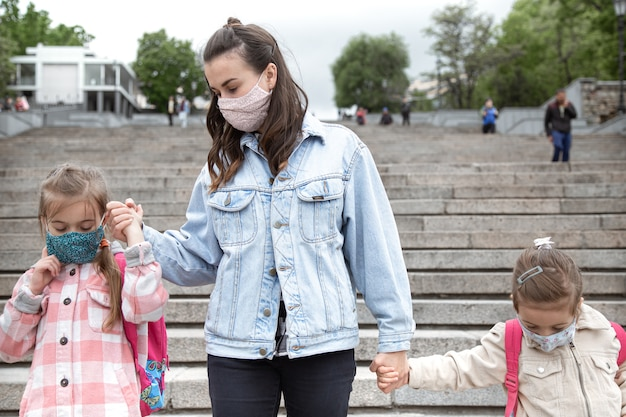 Di nuovo a scuola. i bambini della pandemia di coronavirus vanno a scuola in maschera. madre mano nella mano con i suoi figli.