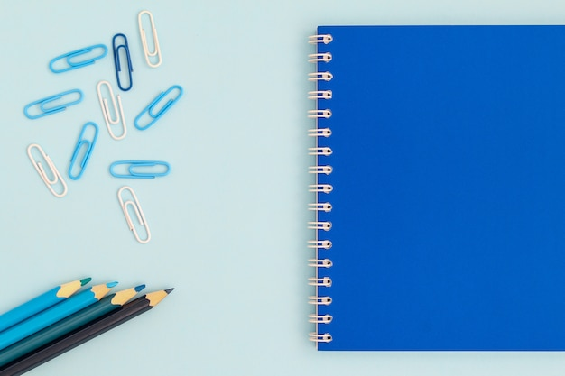 Back to school creative . blue notebook with pencils and clips on a blue background top view of a flat lay.