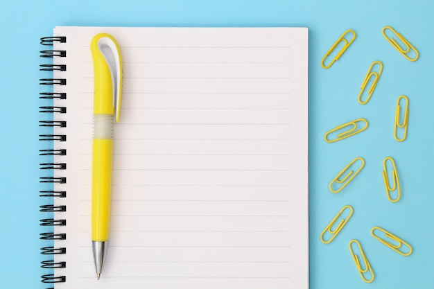Back to school creative . notepad with yellow pen and clips on a blue background.