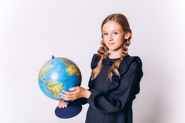 Back to school. cute adorable caucasian blondie girl in school uniform with globe on white background