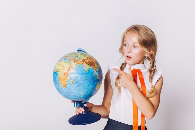 Back to school. cute adorable caucasian blondie girl with globe in school uniform on white background