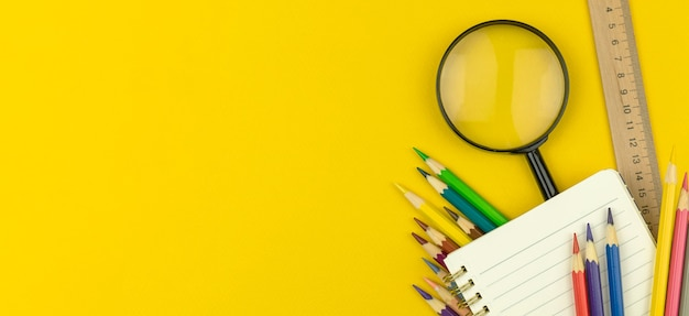 Back to school and education concept banner with notepad, color pencils and magnifying glass on the yellow table, top view and copy space photo