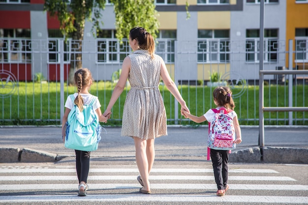 Back to school education concept with girl kids, elementary students, carrying backpacks going to class  holding hand in hand together walking