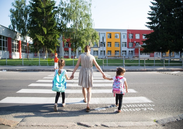 Back to school education concept with girl kids, elementary students, carrying backpacks going to class