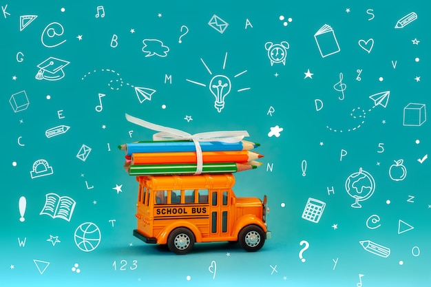 Back to school and education concept. yellow retro school bus carryies pencils on roof on blue background with school stationery.