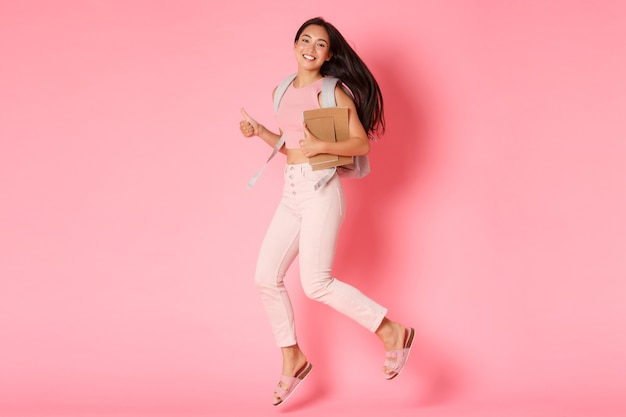 Back to school, education and lifestyle concept. full length of happy smiling asian female student, girl from college jumping with notebooks and backpack, showing thumbs-up in approval, pink wall