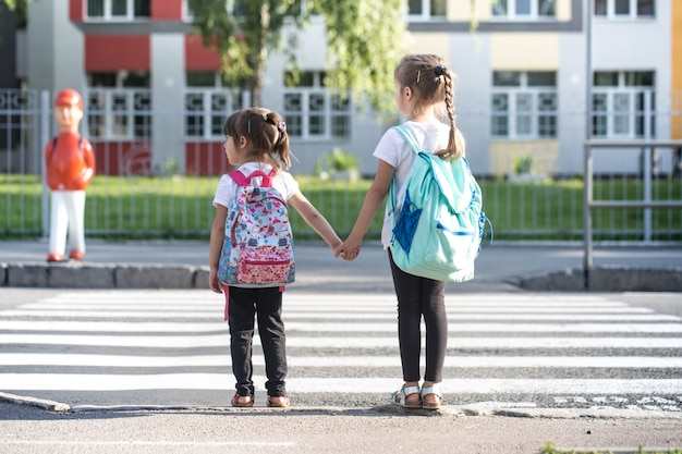Back to school education  with girl kids, elementary students, carrying backpacks going to class