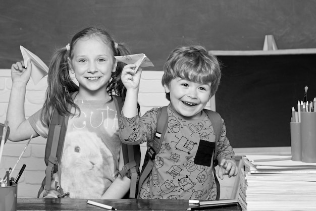 Back to school. elementary school and education. child play with paper airplane near chalkboard in