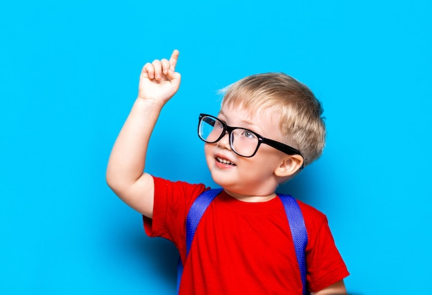 Back to school first grade junior lifestyle. small boy in red t-shirt. close up studio photo portrait of smiling boy in glasses with schoolbag, pointing up with his finger