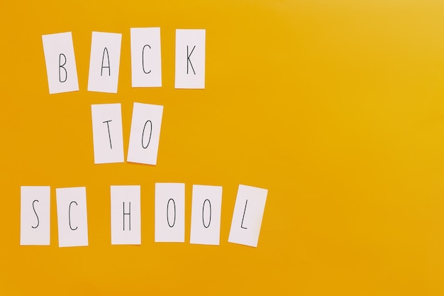 Back to school flat lay on orange background. letters on stickers.