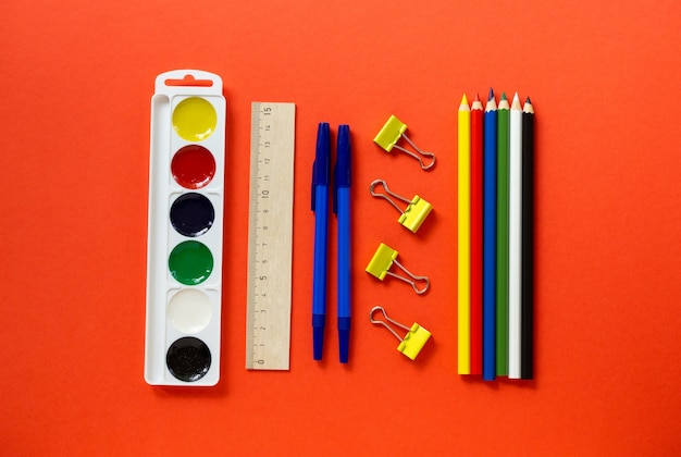 Back to school flat lay. set of stationery on a red background, top view