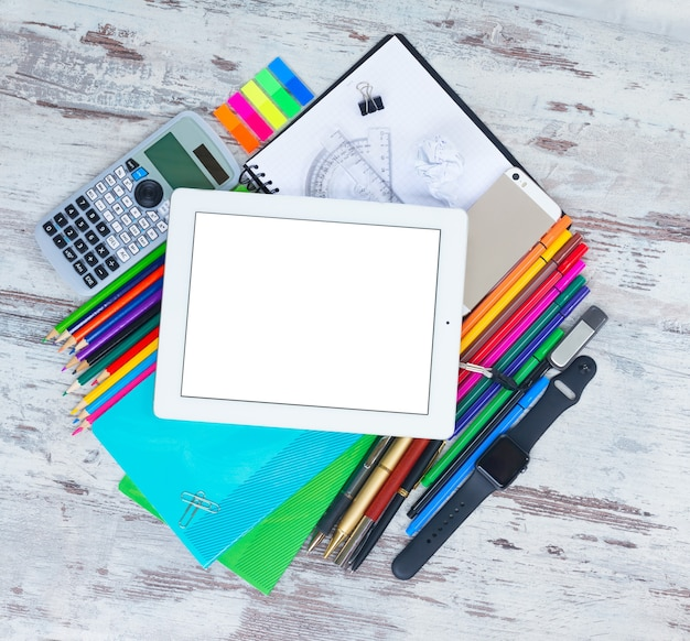 Back to school frame with school supplies and electronic device tablet on wooden table