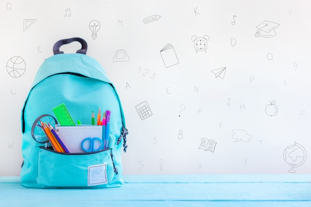 Back to school. full turquoise school backpack with stationery on table.