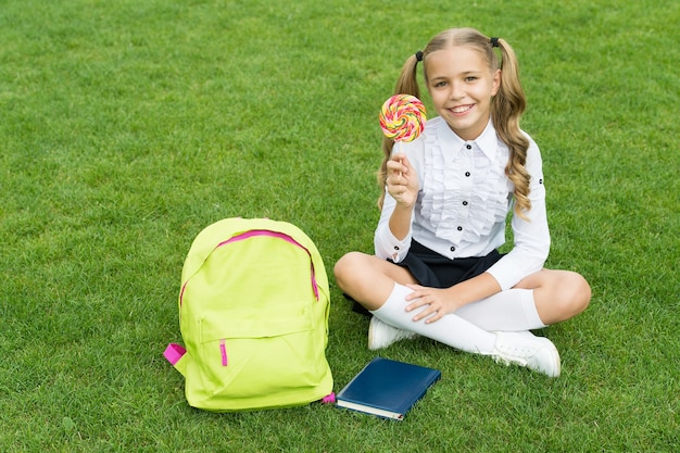 Back to school funny child hold lollipop concept of education ordinary learning day cute girl