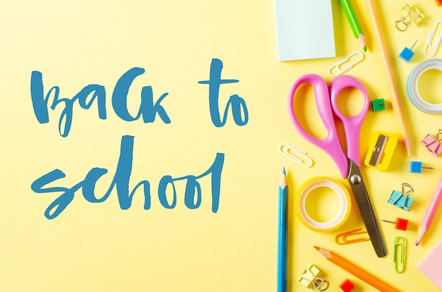 Back to school. handwritten inscription. school supplies on a yellow paper background.