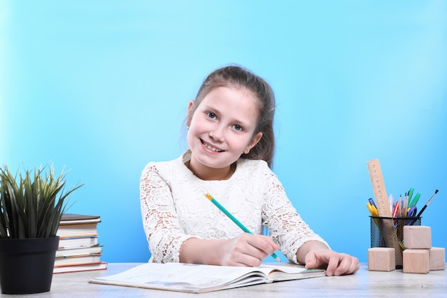 Back to school .happy cute industrious child is sitting at a desk indoors