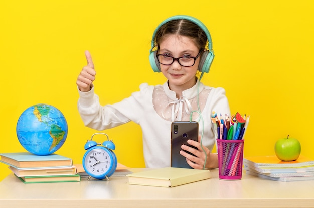 Back to school and happy time. cute industrious child is sitting at a desk indoors. kid is learning in class on yellow background. happy smiling little girl with thumb up