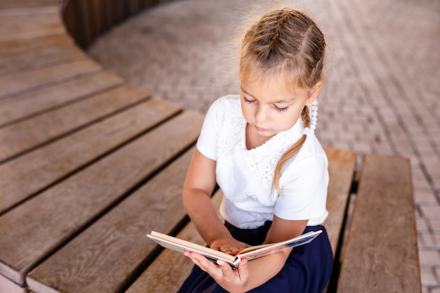Back to school and happy time cute industrious child sitting outdoors. girl reading the book.