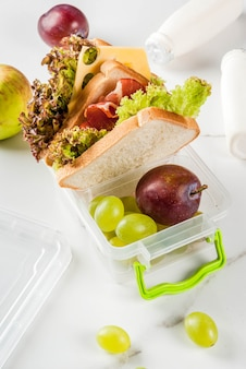Back to school. a healthy lunch in a box is fresh fruit apples, plums, grapes, a bottle of yogurt and a sandwich with leaves of lettuce, tomatoes, cheese, meat. on a white marble table.