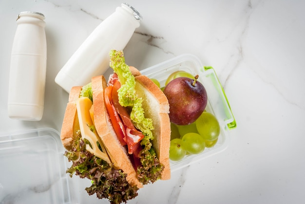 Back to school. a healthy lunch in a box is fresh fruit apples, plums, grapes, a bottle of yogurt and a sandwich with lettuce, tomatoes, cheese, meat. white marble table.  top view