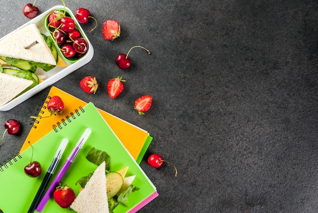 Back to school. a hearty healthy school lunch in a box: sandwiches with vegetables and cheese, berries and fruits apples with notebooks, colored pens on a black table.